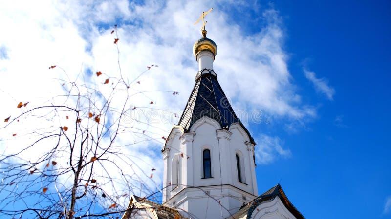 Weiße Kirche gegen blauen Himmel mit goldenen Hauben Gesamtl?nge auf Lager Ansicht des Golden Domes des Tempels gegen das Blau stockfoto