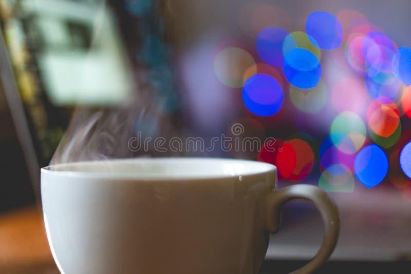Weiße klassische Schale mit heißem Getränk mit Dampf kommen auf Arbeitsplatztabelle f heraus lizenzfreie stockfotos