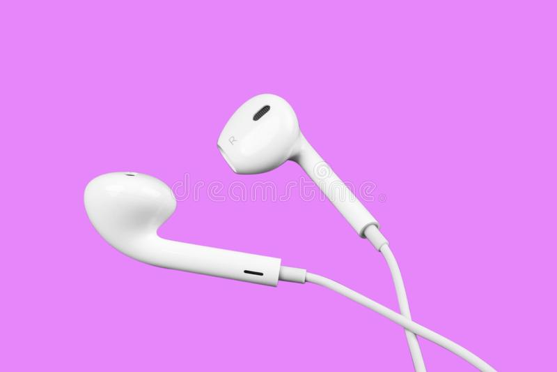 Weiße kleine Kopfhörer lokalisiert auf purpurrotem Hintergrund Kopfhörer lokalisiert auf schwarzem Hintergrund lizenzfreies stockfoto