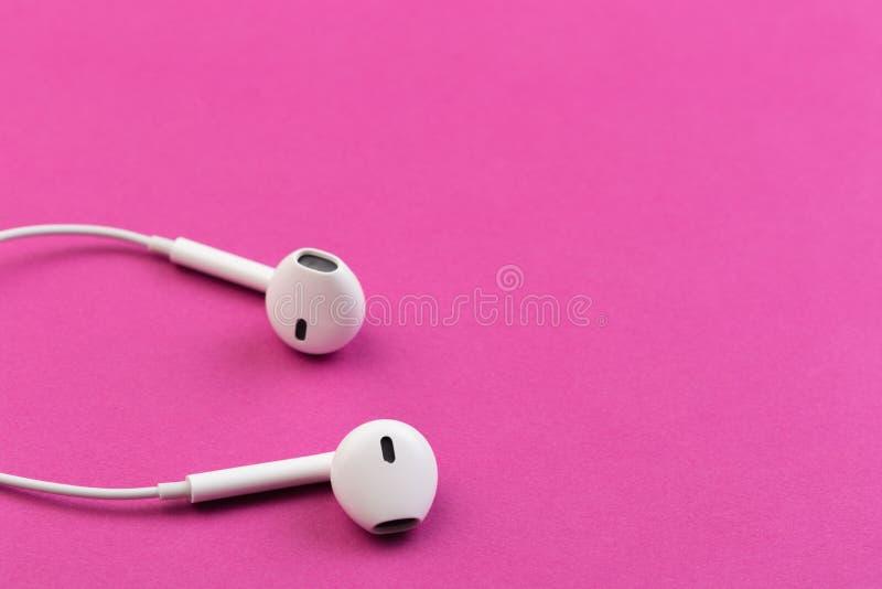 Weiße Kopfhörer auf violettem Hintergrund stockfotografie