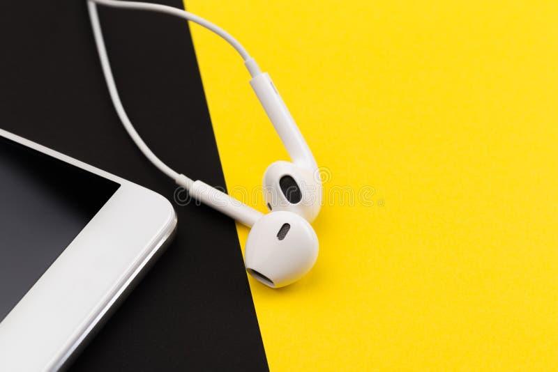 Weiße Kopfhörer mit Telefon auf schwarzem und gelbem Hintergrund lizenzfreies stockbild