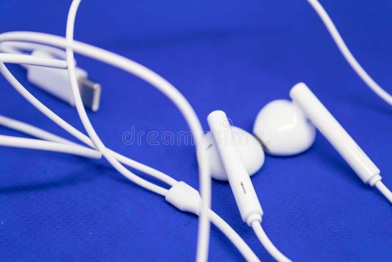 Weiße Kopfhörer mit Verbindungsstück auf blauem Hintergrund - Bild stockfotografie