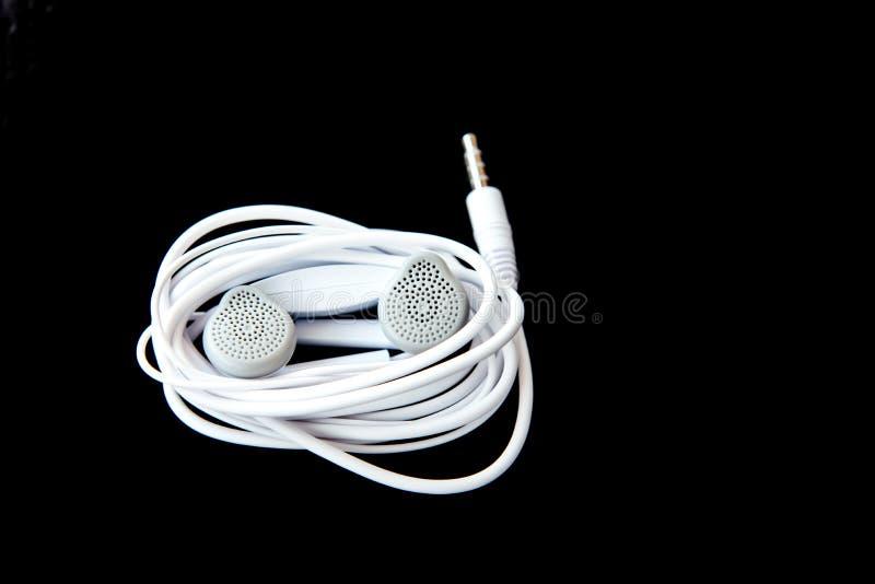 Weiße Kopfhörer, Ohrenpfropfen lizenzfreie stockfotos