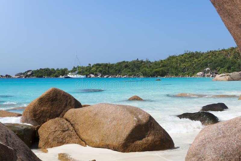 Weiße korallenrote Strandsand und der Azurblauindische ozean. Segeljacht an lizenzfreies stockfoto