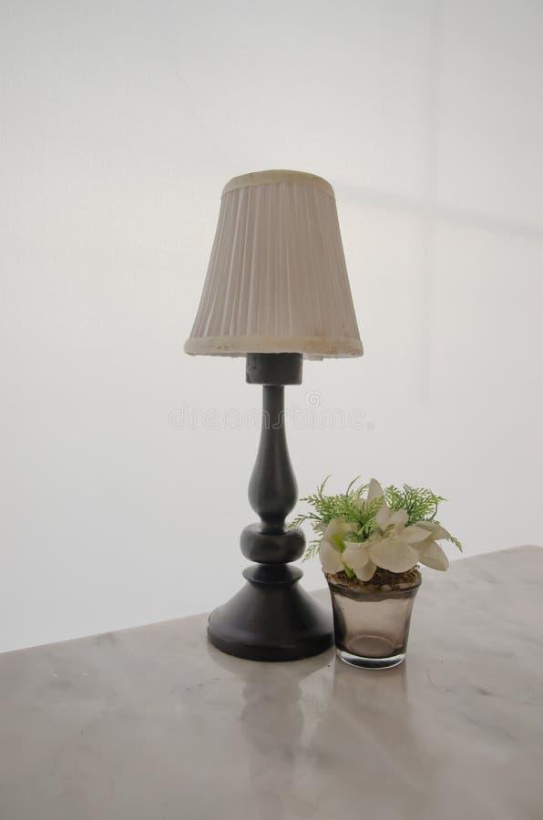 Weiße Lampe und Blume verzieren auf Tabelle stockfotografie