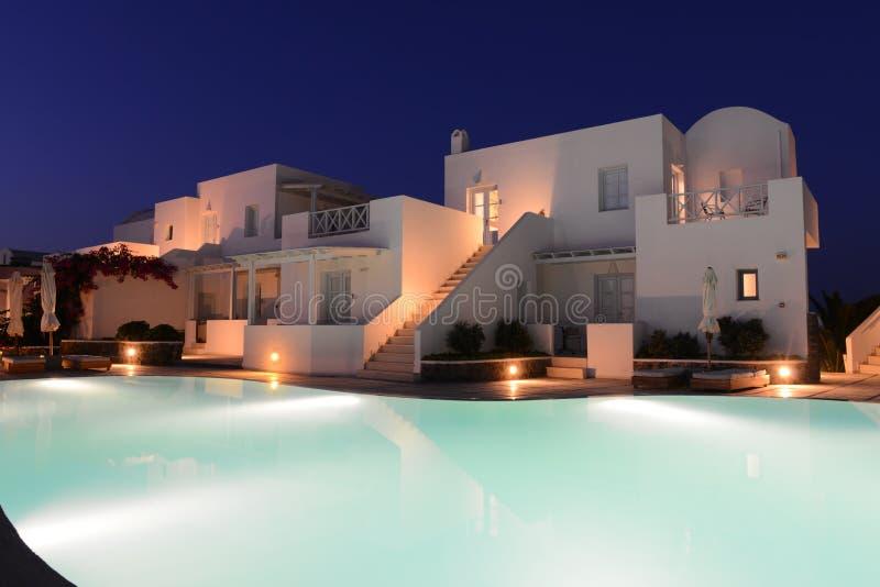 Weiße Landhäuser nähern sich Pool eines Luxus-Resorts nachts stockfotografie