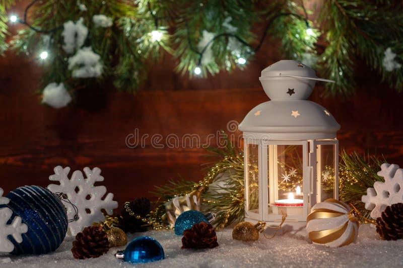 Weiße Laterne mit einer brennenden Kerze steht im Schnee, der durch Weihnachtsdekorationen auf dem Hintergrund von einem hölzerne stockfotografie