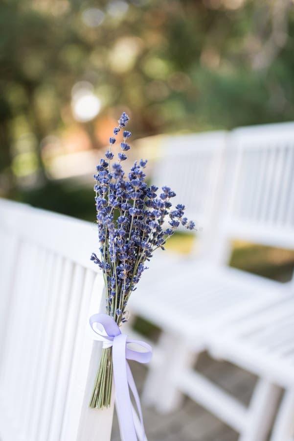 Weiße Lavendelblumen nah oben gesehen Rückenlehne eines Stuhls verziert mit einem Blumenstrauß des Lavendels Hochzeitsstuhl verzi lizenzfreies stockfoto