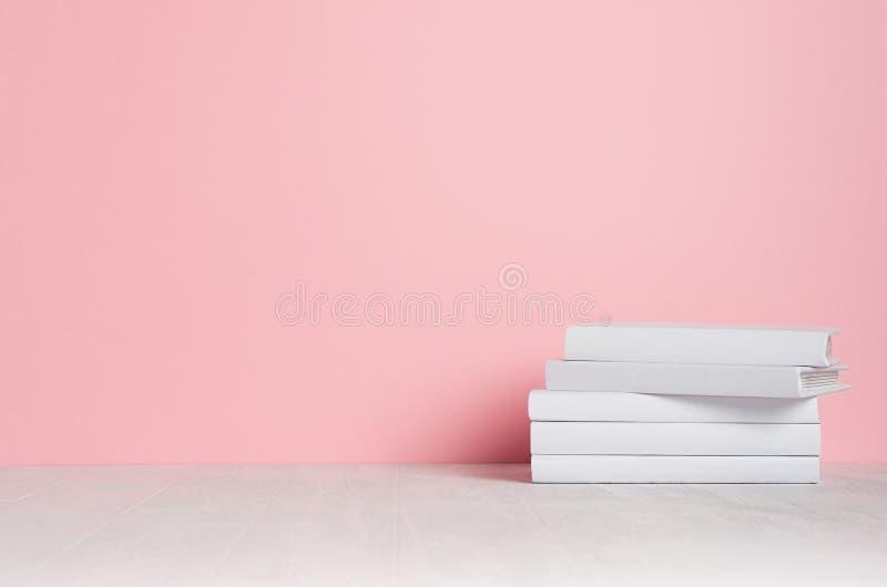Weiße leere Bücher auf weißem Regal und weicher rosa Wand als modernem, elegantem Hauptdekor stockfotografie