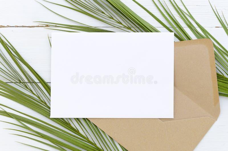 Weiße leere Karte und Umschlag der minimalen Zusammensetzung auf Palmblättern auf einem weißen hölzernen Hintergrund Modell mit U lizenzfreie stockbilder