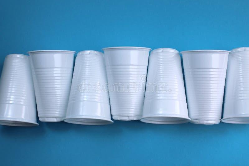 Weiße leere Plastikgläser in Folge ausgebreitet stockbilder