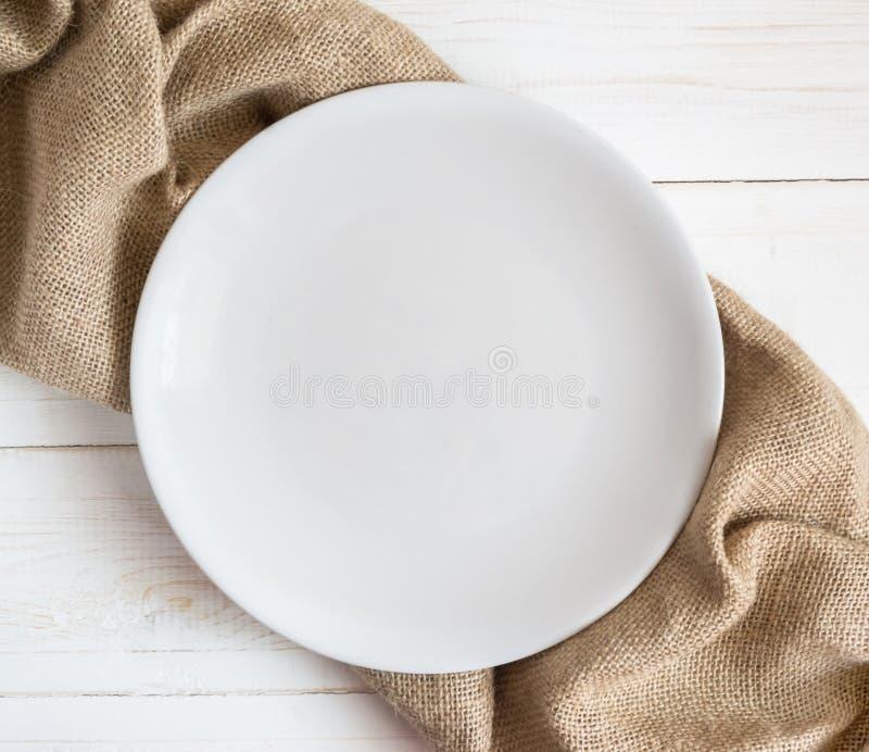 Weiße leere Platte auf Holztisch mit brauner Serviette stockfoto