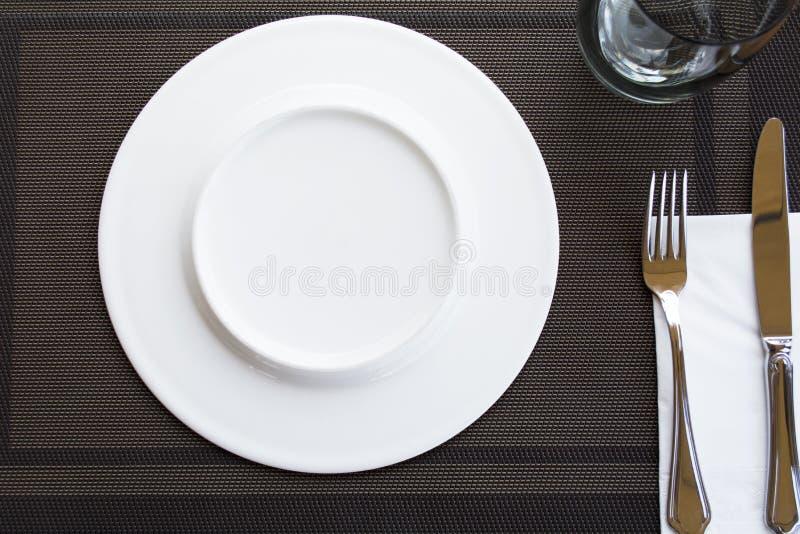 Weiße leere Platten mit der Gabel und Messer gebunden mit einem Band stockbilder