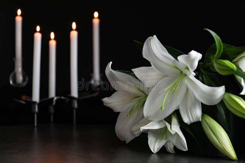Weiße Lilien und unscharfe brennende Kerzen auf dem Tisch in Dunkelheit, in der Nähe Platz für Text stockbilder