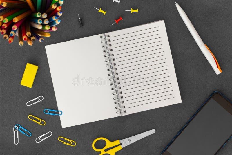 Wei?e Linie Spiralenpapiernotizbuch mit Handy, Stift, farbigen Bleistiften, Radiergummi, B?roklammern und Scheren auf dunklem Hin stockbild