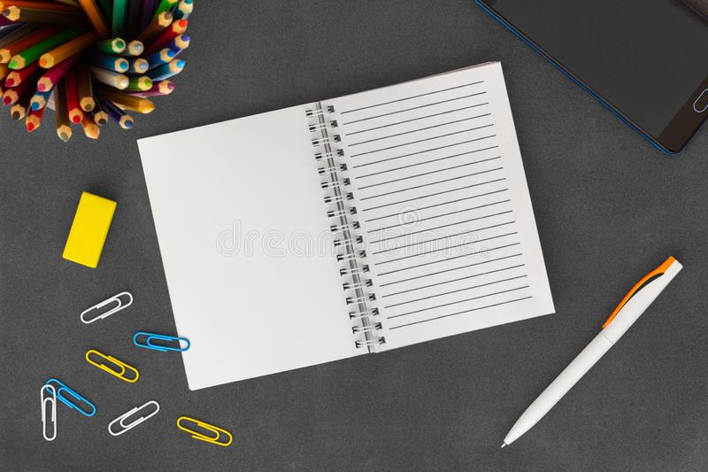Weiße Linie Spiralenpapiernotizbuch mit Handy, Stift, farbigen Bleistiften, Radiergummi und Büroklammern auf dunklem Hintergrun stockfoto