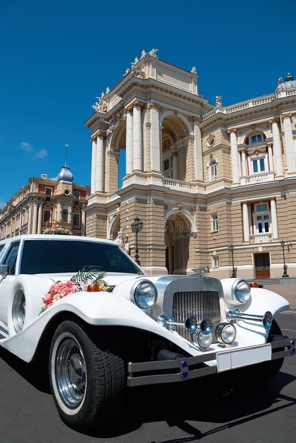 Weiße Luxuslimousine der Hochzeit, die vor einem Palast erwartet lizenzfreies stockfoto