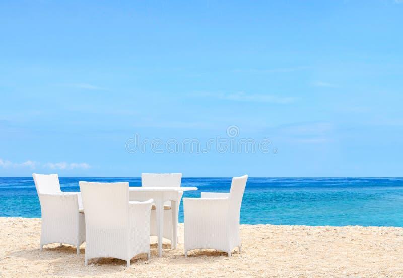 Weiße Luxusstühle und Tabelle auf weißem sandigem Strand lizenzfreies stockbild