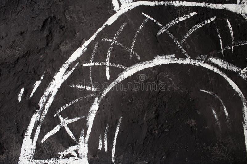 Weiße Malerei auf einer schwarzen Wand lizenzfreie stockfotografie