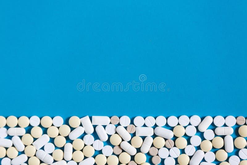 Weiße medizinische Pillen auf blauem Hintergrund mit Kopie-Raum Beschneidungspfad eingeschlossen Hand, die lego Wand aufbaut lizenzfreie stockfotos