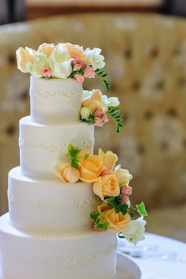 Weiße mehrstufige Hochzeitstorte mit Blumendekorationen, Unschärfe-BAC stockfoto