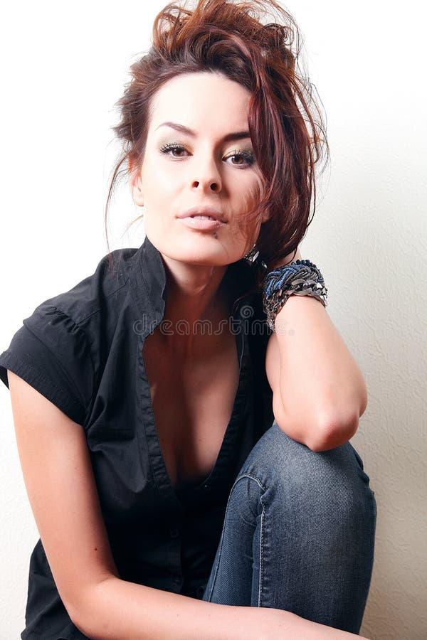 Weiße Modefrau, braunes schönes langes Haar und Augen in der schwarzen Weste, Blue Jeans stockfotos