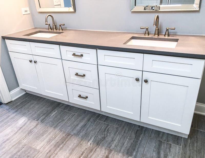 Weiße moderne Badezimmerkabinette mit Quarz Countertop, zwei Wannen und Hähnen mit Steinboden lizenzfreie stockbilder