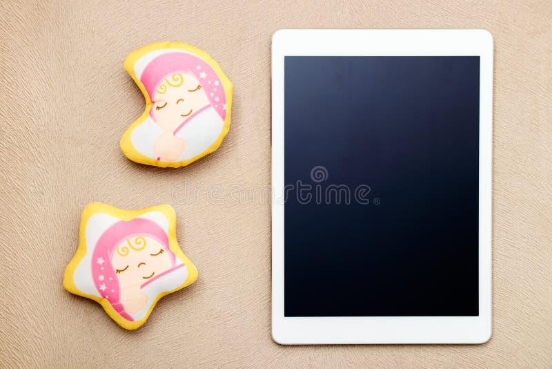 Weiße moderne digitale Tablette und Baby spielen auf Gewebebeschaffenheit stockbild