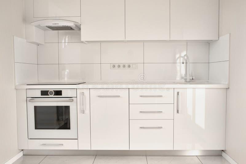 Weiße moderne Küche in der zeitgenössischen Ebene lizenzfreie stockfotografie