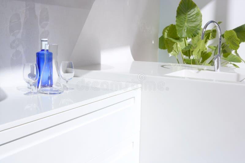 Weiße moderne Küche, Flasche des blauen Wassers und Anlagen lizenzfreie stockbilder
