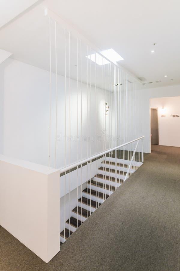 Weiße, moderne Treppe mit Sicherheitstreppe im Innenhof Innere Herberge Hostel Business lizenzfreies stockbild