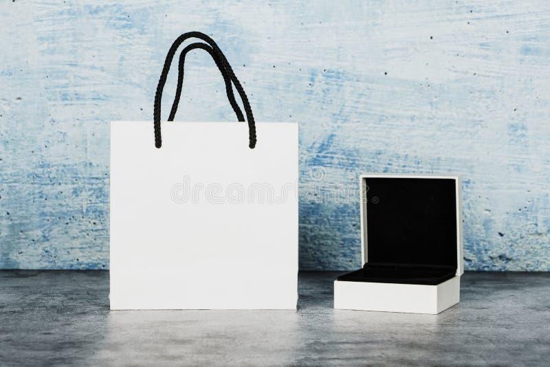 Weiße Papiertasche mit einem Tasse Kaffee auf einem grauen und blauen Hintergrund Abschluss oben Platz für Text Scheinbares hohes stockfotos
