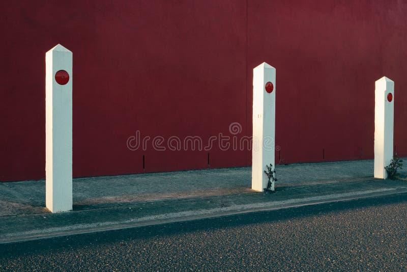Wei?e parkende Pfosten neben einer Stra?e mit einer roten Wand im Hintergrund lizenzfreie stockfotos