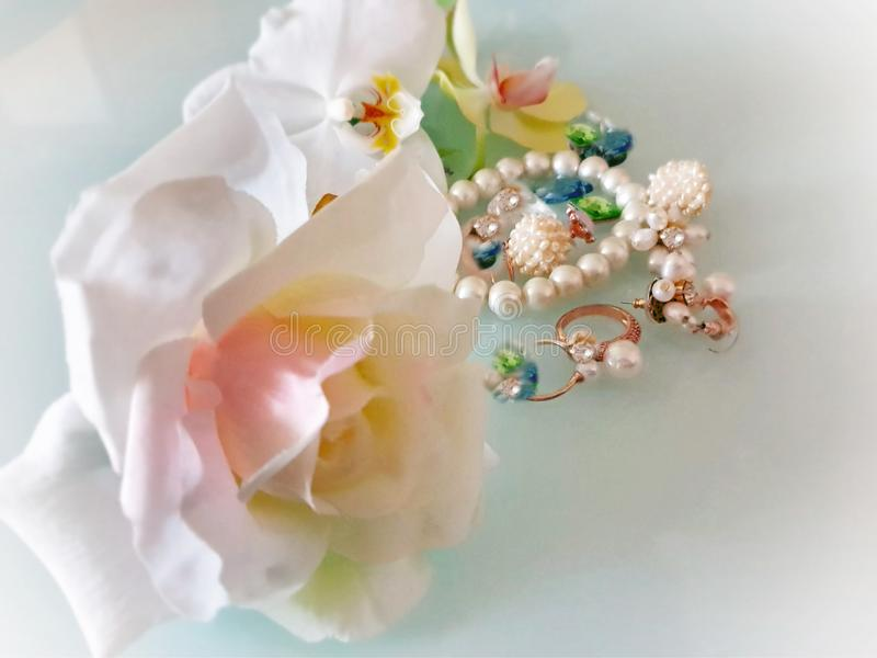 Weiße Perle des Schmucks schellt Ohrringarmband mit roten Rosen des Luxuszaubermodekostümgoldschmucks, Orchideen auf Blauem und stockbild