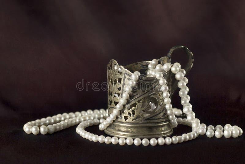 Weiße Perlenhalskette und Silberschale stockfotografie