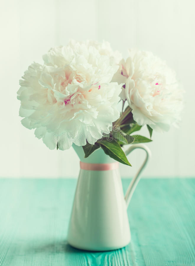 Weiße Pfingstrosen im Blumenvase auf Holztisch, tadellose Farben der Weinlese lizenzfreie stockbilder