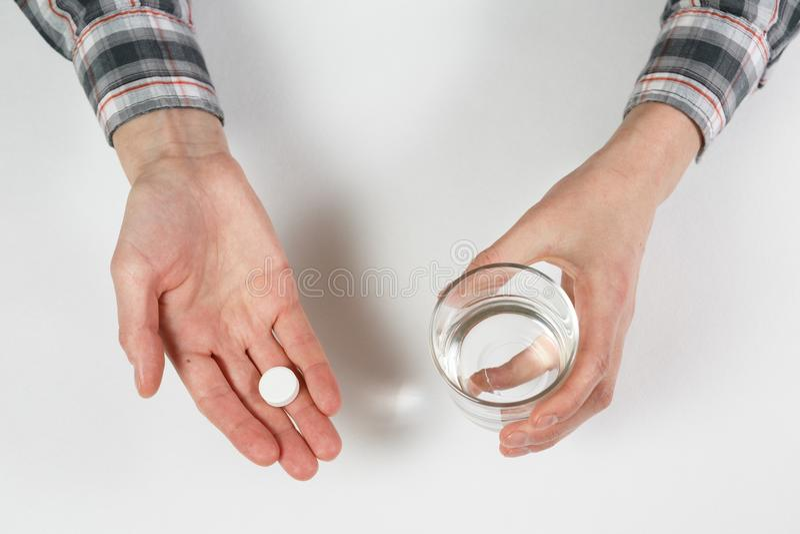 Weiße Pille und ein Glas Wasser in den weiblichen Händen stockbild