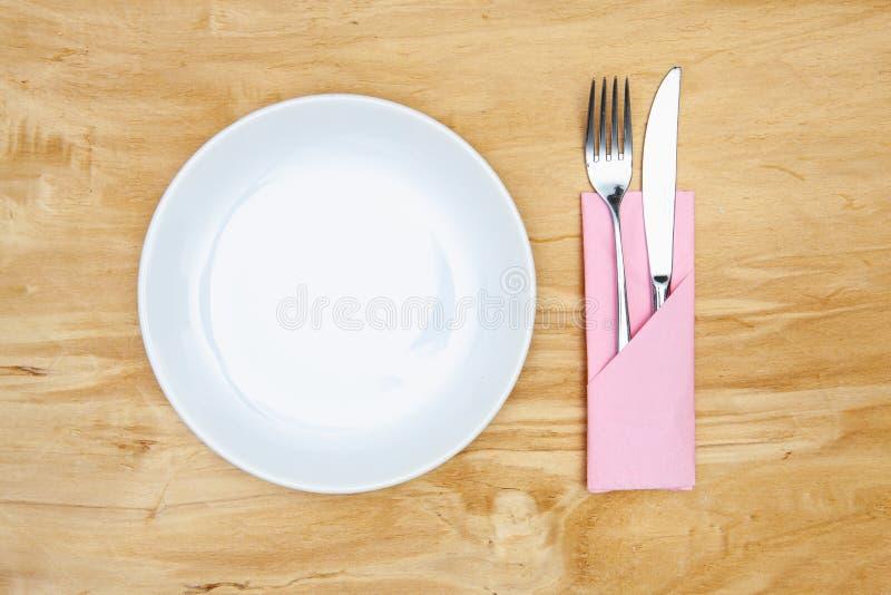 Weiße Platte auf der hölzernen Tabelle lizenzfreies stockfoto