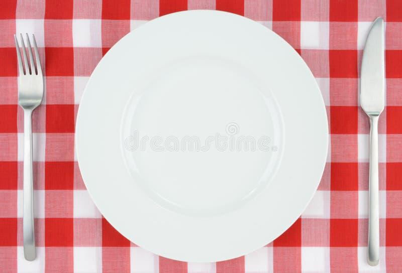Weiße Platte auf rotem und weißem kariertem Stoff