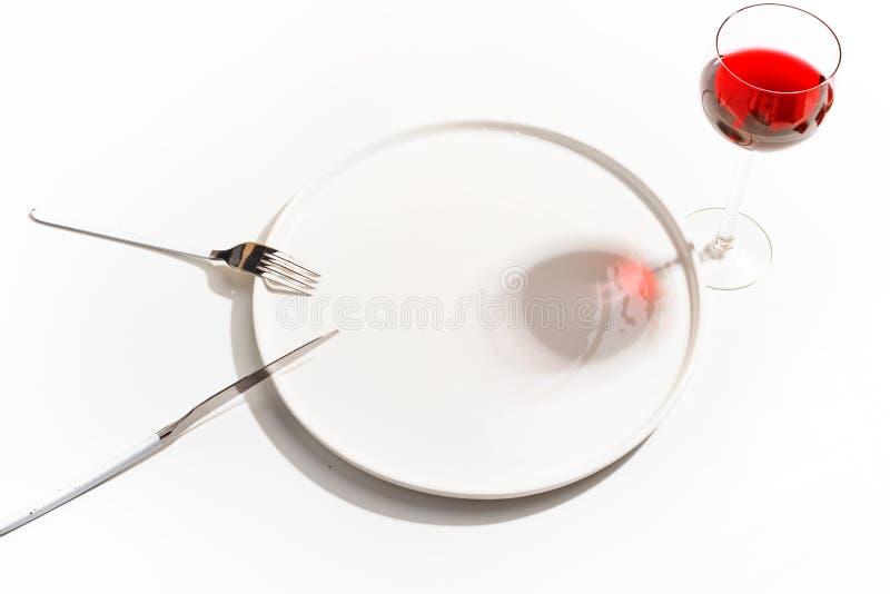 Weiße Platte, Messer, Gabel und ein Glas Rotwein auf einem hellen Hintergrund Beschneidungspfad eingeschlossen Minimalistic-Konze stockfoto