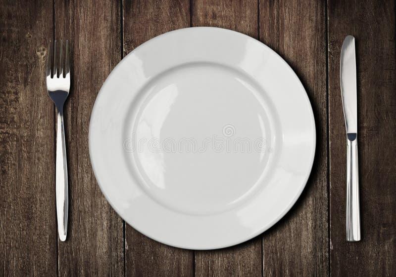 Weiße Platte, Messer und Gabel auf altem Holztisch lizenzfreie stockfotos
