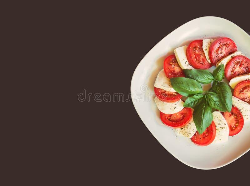 Weiße Platte mit caprese Salat mit reifen Tomaten, Mozzarellakäse und grünen Basilikumblättern stockbilder