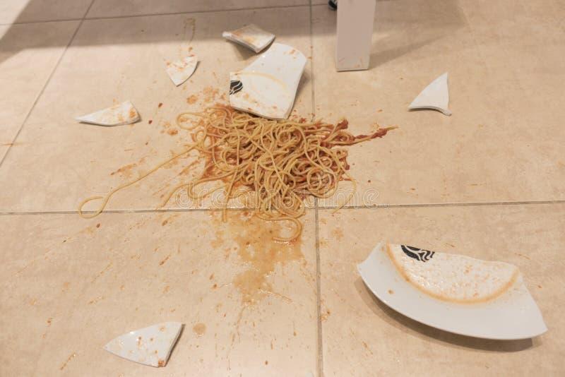 Weiße Platte mit den Teigwaren gebrochen auf keramischem Boden in der Küche, inländischer Lebenunfall lizenzfreie stockbilder
