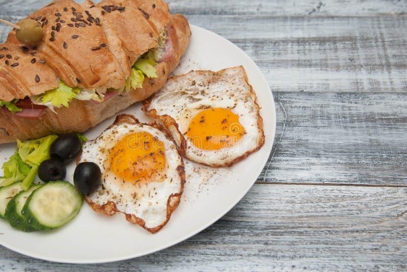 Weiße Platte mit Fried Eggs und Hörnchen-Sandwich mit Gurke, Tomatoe und Oliven Frühstück Gray Wooden Background Rustikales St. stockbilder