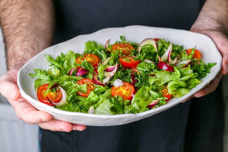 Weiße Platte mit Kopfsalat, Kirschtomaten und Salat der roten Zwiebel stockbild