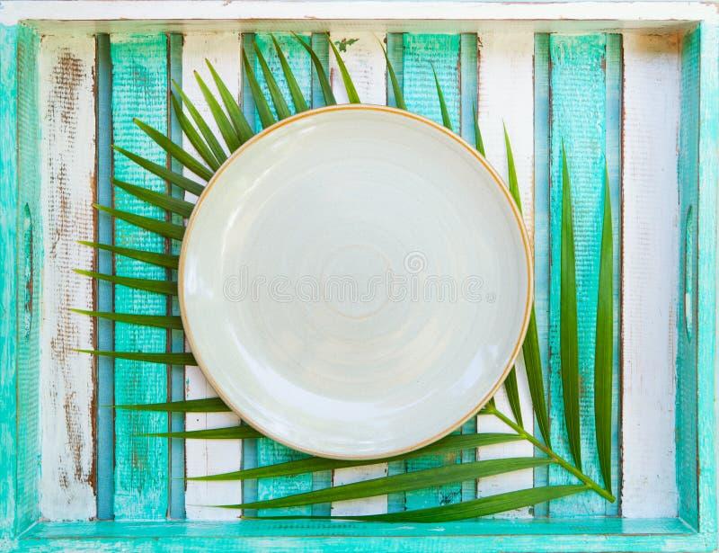 Weiße Platte mit Palmblatt auf hölzernem Hintergrund Kopieren Sie Platz Beschneidungspfad eingeschlossen lizenzfreies stockbild