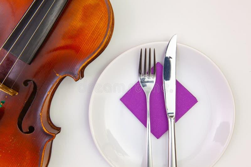 Weiße Platte und alte Violine auf dem weißen Holztisch lizenzfreie stockfotos