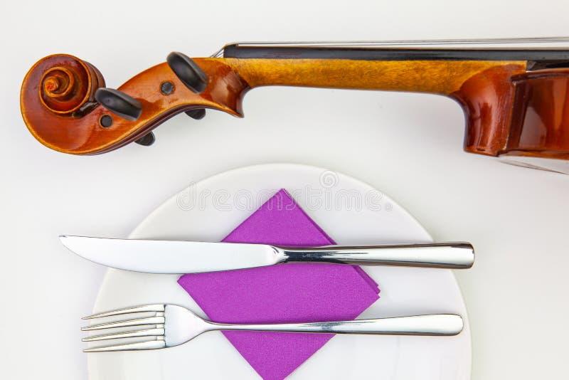 Weiße Platte und alte Violine auf dem weißen Holztisch stockbild