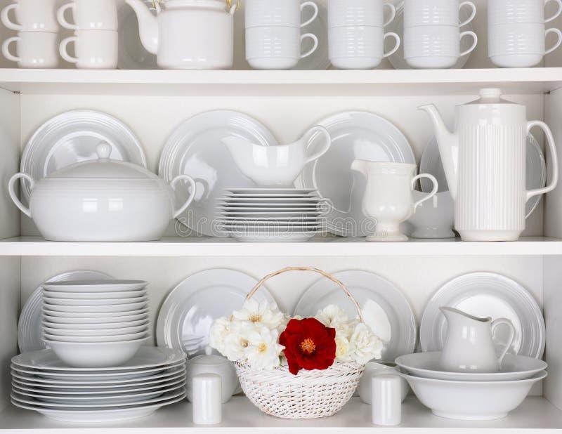 Weiße Platten im Schrank mit einem Korb von Rosen lizenzfreie stockbilder