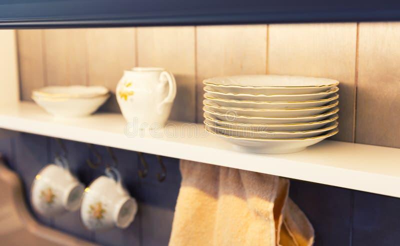 Weiße Platten und Essgeschirr in einem Schrank stockbild